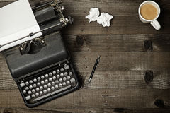 Writers Block. Old fashioned typewriter on wood desktop with coffee and pen and two crumples pieces of paper Royalty Free Stock Photography