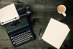 Writers Block. Old fashioned typewriter on wood desktop with coffee and pen and two crumples pieces of paper and sheets of blank paper Stock Photography