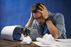 Writers Block. Portrait of frustrated bearded man struggling with writers block over typewriter stock photo