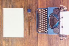 Writers Block. Typewriter with Empty Ark of Paper and Empty Notebook on Wooden Desk Stock Photography