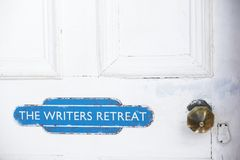 Writers retreat door sign at entrance to quiet room on white weather oak door distressed paint. Uk royalty free stock photography