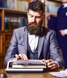 Writers routine concept. Author types novel or poem. Writer working on new book with bookshelves on background. Man with beard and busy face sit in library and stock images
