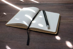 The writers set 01. Sunbeam on opened empty notebook with black pen and bookmark on wodden table, close up Royalty Free Stock Photography