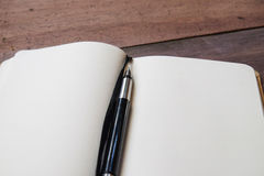 The writers set 03. Top of opened empty notebook with black fountain pen and bookmark on wodden table, close up Stock Photos