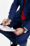 Writes the document. Businessman with a clock on the hand writes the document Stock Photo