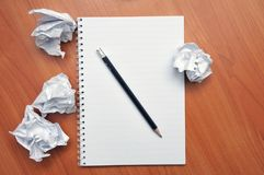 Writes in a notebook around a crumpled paper royalty free stock photography
