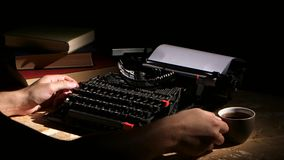 Writes typing a typewriter at night creates a new novel. Writes on a typewriter creates a new novel at night, on the table lie old books and a cup of tea stock video footage