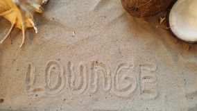 Writes the word lounge, on the sand of the beach with a seashell and a coconut. Royalty Free Stock Photos