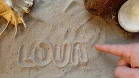 Writes the word lounge, on the sand of the beach with a seashell and a coconut stock video footage