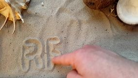 Writes the word relax, on the sand of the beach with a seashell and a coconut.  stock video footage