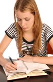 Writing. Young beautiful woman sitting and writing at table Stock Photography