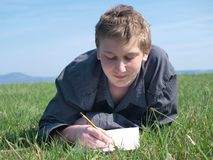 Writing. Portrait of young blond smiling man writing or drawing on the blank paper (wearing grey shirt) laying in the grass in the sun Stock Photo