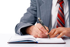 Writing. Close-up picture of businessman's hands writing in the dairy Royalty Free Stock Photos