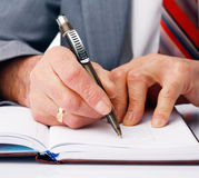 Writing. Close-up picture of businessman's hands writing in the dairy Royalty Free Stock Image