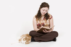 Writing. A beautiful young woman writing in her journal next to her sleeping cat stock photography