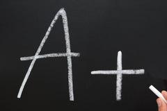 Writing A+. A teacher writing A+ on a blackboard Royalty Free Stock Photo