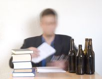 Writing. Alcoholic accountant in his office sorting out documents Stock Images