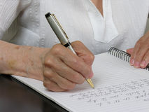 Writing 3. An elder woman writing in notebook Royalty Free Stock Photos