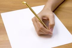 In writing. Female hand holding a golf-club shaped pen and a blank paper Royalty Free Stock Photo