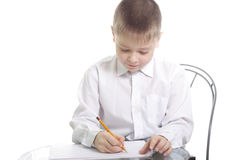 Writing. Kid in white shirt writing on a glass table Stock Image