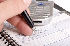 Writing in address book with cell phone royalty free stock photos