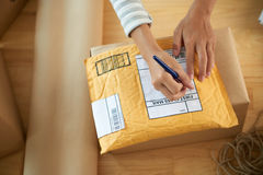 Writing address. Hands of woman writing address on first class mail package Stock Photography