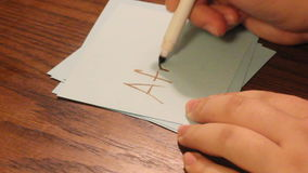 Writing afraid. Young girls hand writes afraid on a white card stock footage