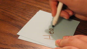 Writing afraid. Young girls hand writes afraid on a white card stock video