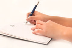 Writing on agenda. Woman hand holding pen and writing on agenda royalty free stock photography