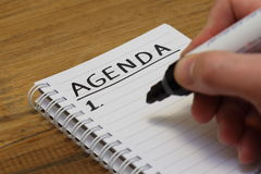 Agenda in spiral bound notebook. Hand holding a broad black marker pen writes text ' agenda ' in bold uppercase letters on top line of spiral bound notebook stock images