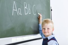 Writing alphabet. Young smiling boy writing alphabet on chalkboard. He's looking at camera Stock Photos
