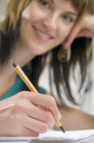 Writing ans smile. Young female is writing notes and planning her schedule stock images