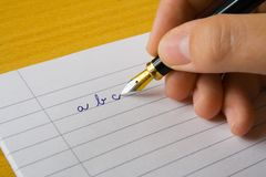 Writing arm. Arm writes on paper pen abc Stock Photography