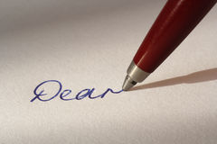 Writing with ballpoint pen. Handwritten 'Dear' with pen and paper Stock Photography