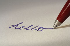 Writing with ballpoint pen. Handwritten 'Hello' with pen and paper royalty free stock photo