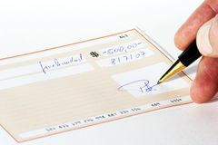 Writing a bank check. Man writing and signing a bank check with a pen Stock Photography