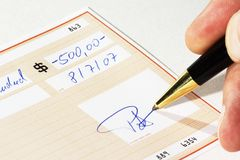 Writing a bank check. With a ball pen Stock Photography