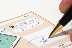Writing a bank check. With a ball pen, credit card on the left Royalty Free Stock Photos