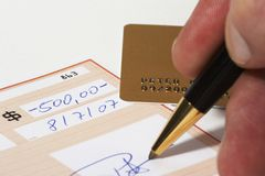 Writing a bank check. With a ball pen, gold card in background Royalty Free Stock Photo