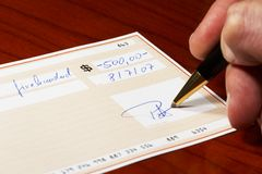 Writing a bank check. With a ball pen Royalty Free Stock Images