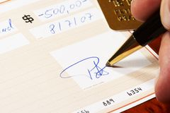 Writing a bank check. With a ball pen, gold card in background Stock Images
