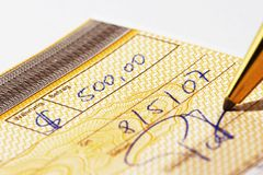 Writing a bank check. With a pen Royalty Free Stock Photo