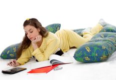 Writing in bed. Beautiful young woman in pajamas study in bed Royalty Free Stock Images