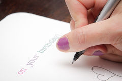 Writing birthday card. Close up of a woman's hand writing a birthday card Stock Photo