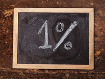Writing 1% on a blackboard with white chalk on wooden background Stock Image