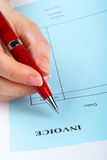 Writing blank invoice with pen Royalty Free Stock Photo