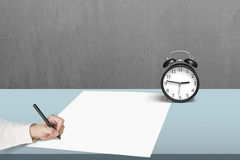 Writing on blank paper with alarm clock Stock Photography
