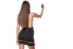 Writing in blank. Rear view of a pretty girl in short black dress writing in blank with a marker stock images