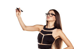 Writing in blank. Serious woman with glasses writing with a marker in the empty space royalty free stock photos