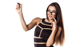 Writing in blank. Serious woman with glasses writing with a marker in the empty space royalty free stock images